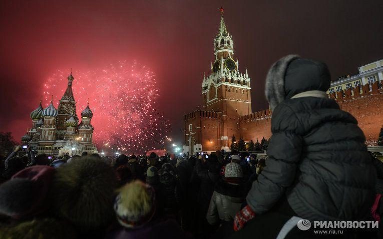 Москвичи и гости столицы смотрят праздничный фейерверк на Красной Площади