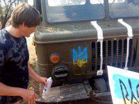 Фотофакт: Запорожский активист украшает военную технику желто-синими гербами Украины