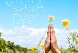 closeup of the hands of a young caucasian yogi man meditating outdoors in anjali mudra and the text yoga day