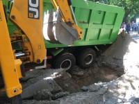 В Запорожье грузовик рассыпал по дороге песок, застряв в яме (Фото)